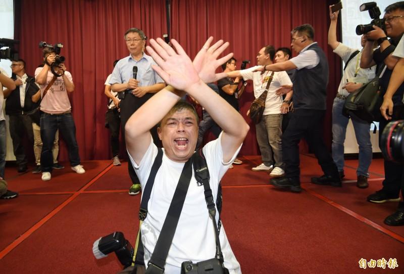 台北市長柯文哲今(6)日在台大醫院國際會議中心舉行「台灣民眾黨」創黨大會,並獲選為黨主席。根據新聞畫面顯示,「黑色島國青年陣線」核心成員賴品妤被列在黨員名冊中。對此,賴品妤激動澄清,自己不是該黨成員,更直言,「這是妨害名譽!」圖為柯文哲的貼身攝影「金牌」(今)在「民眾黨」創黨成立大會中出面管控秩序。(記者劉信德攝)