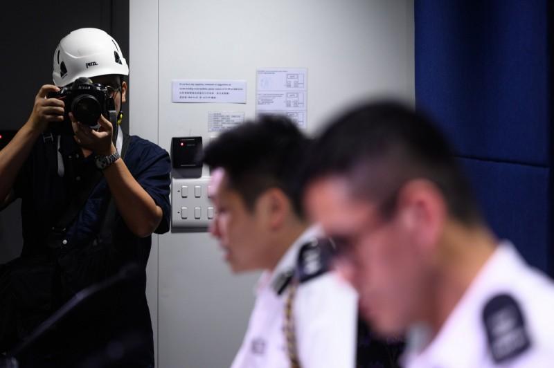 香港記者協會今日在港警記者會發起抗議行動,戴頭盔譴責「警方濫用武力,阻礙記者採訪」。(法新社)