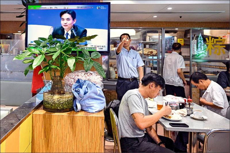中國國務院港澳事務辦公室六日二度針對香港情勢召開記者會,圖為香港一家餐廳裡的電視播出記者會實況。(法新社)