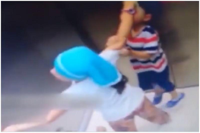 電梯啟動,男孩隨著繩子突然被掛到電梯門上方,男童姐姐除了馬上抬起他的雙腳,更按下緊急按鈕,成功救下差點勒斃的男孩。(圖取自推特)