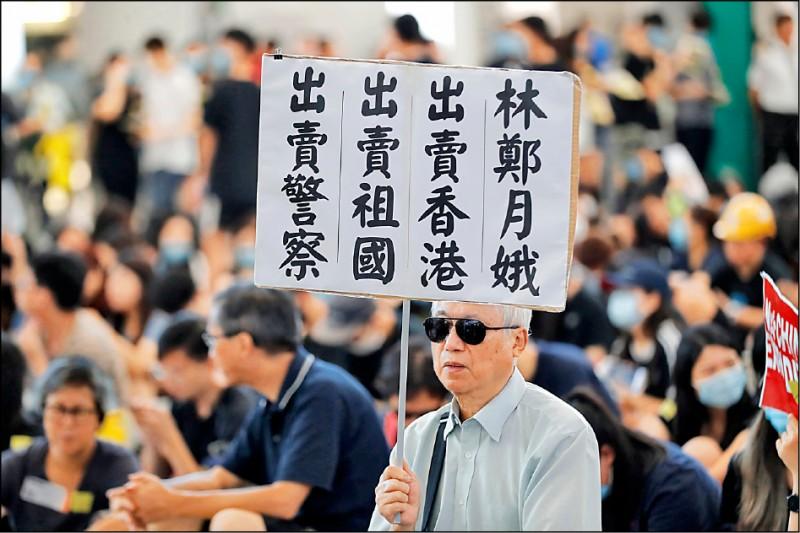 香港國際機場九日舉行反送中的和平靜坐集會,一名戴墨鏡的銀髮族舉著自製標語,批評香港特首林鄭月娥。(美聯社)