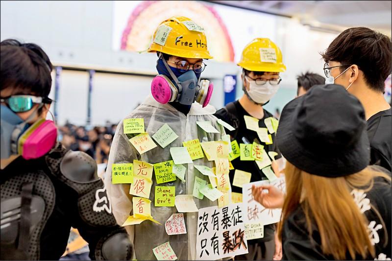 幾名年輕男子戴著反送中示威中常見的口罩、防毒面具和工程安全帽,九日站在香港國際機場內,化身「藍儂牆」,讓民眾在他們身上貼「沒有暴徒、只有暴政」等表達反送中訴求的便利貼。(彭博)