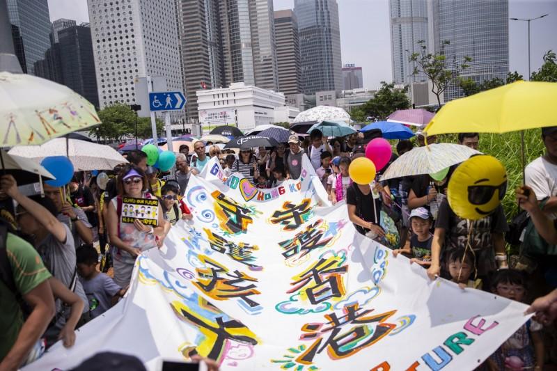 群眾手拉著「守護香港,守護孩子」的大旗,遊行至香港政府總部表達心聲。(歐新社)