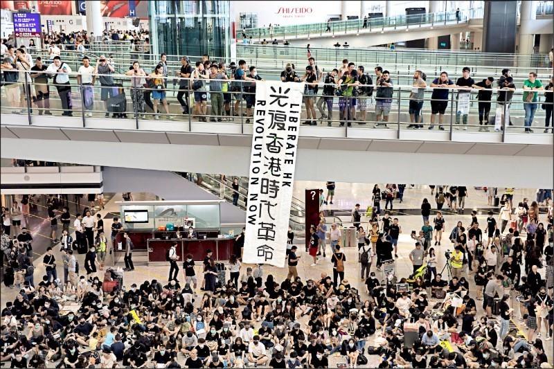 反送中示威者九日在香港國際機場離境層天橋,掛起寫有「光復香港 時代革命」的中、 英文標語。(歐新社)