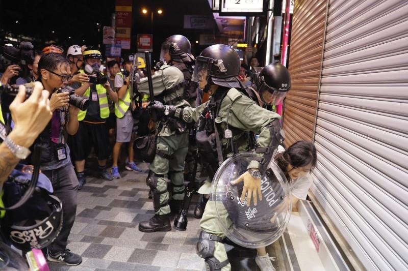 10日「大埔上街」遊行中,一名少女只是路過當地,就遭港警撲倒壓制,過程中還扯其衣,摸其大腿內側,讓現場目睹此幕民眾怒不可遏。(美聯社)