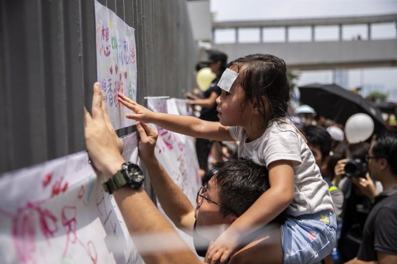 香港民眾發起「反送中」親子遊行,不少爸爸媽媽帶著孩子上街表達意見。(歐新社)