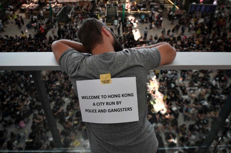香港警方一連反對週末的4場遊行。圖為9日香港機場萬人接機活動中,一位民眾背後貼著「歡迎來到香港,一個由警察與黑幫管治的城市」的標語。(法新社)