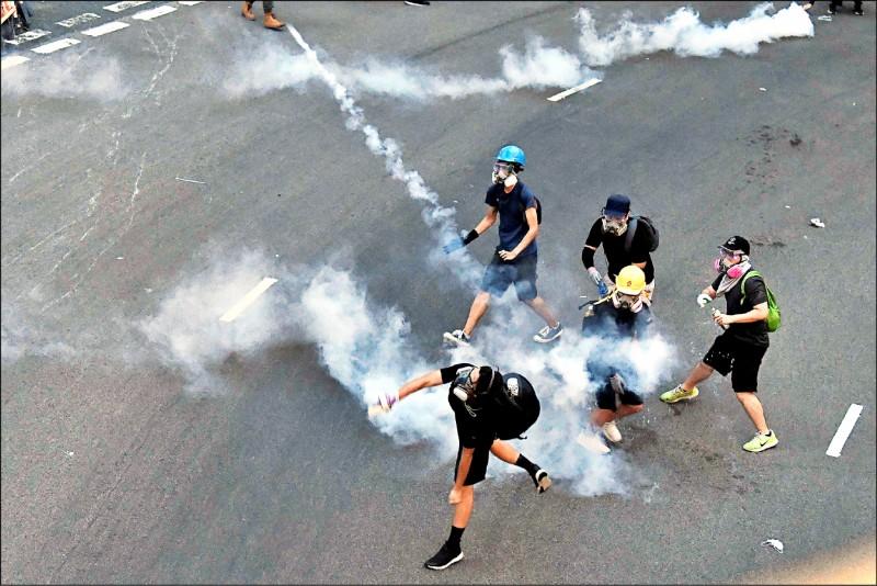 示威者十日在新界沙田區大圍撿起催淚彈,扔向負責驅離他們的鎮暴警察。(法新社)