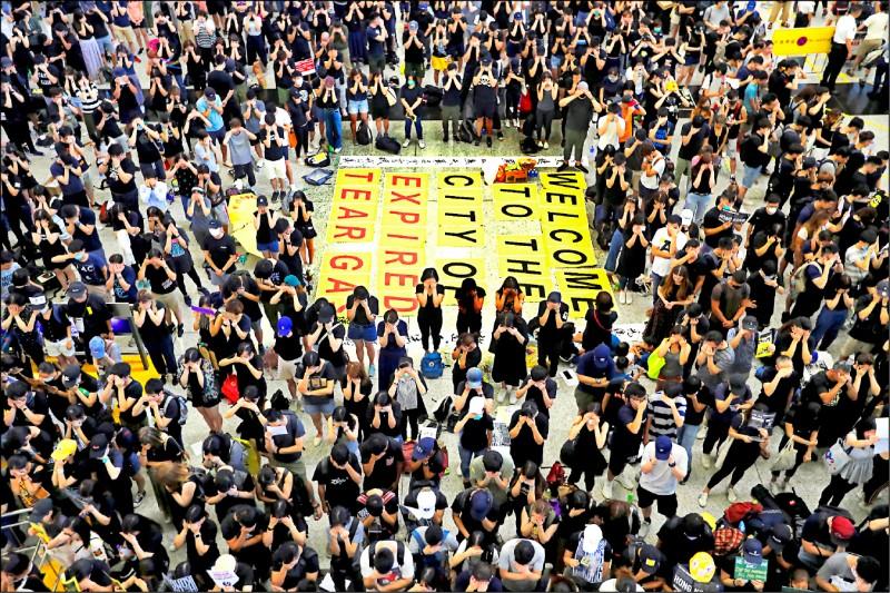 黑衣抗議人士十日在香港國際機場接機大廳地板排出「歡迎來到過期催淚彈之城」的英文標語,諷刺港警使用過期催淚彈對付抗議群眾。(路透)