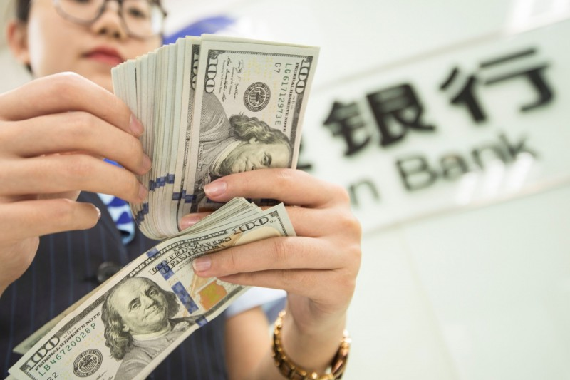 中國一家銀行的女性職員,6日在該銀行位於江蘇南通市的分行點美鈔。(法新社)