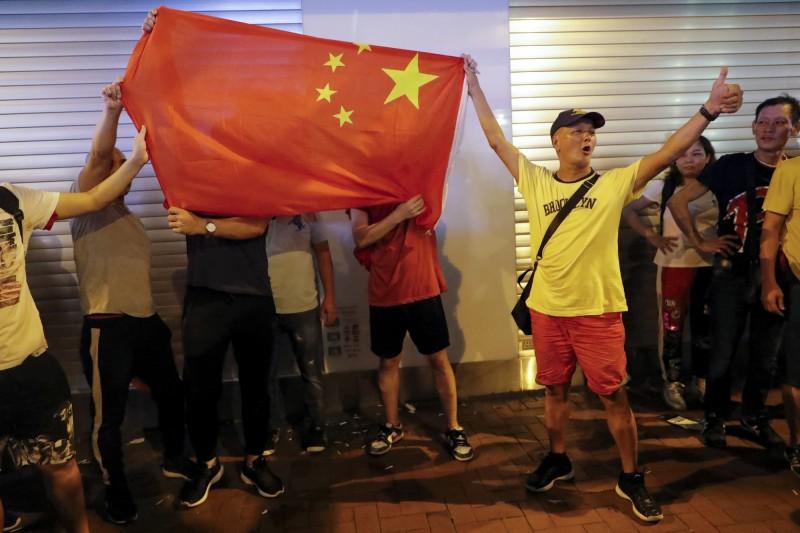 有人在街頭發表「稱警」言論,並揮舞五星旗。(美聯社)