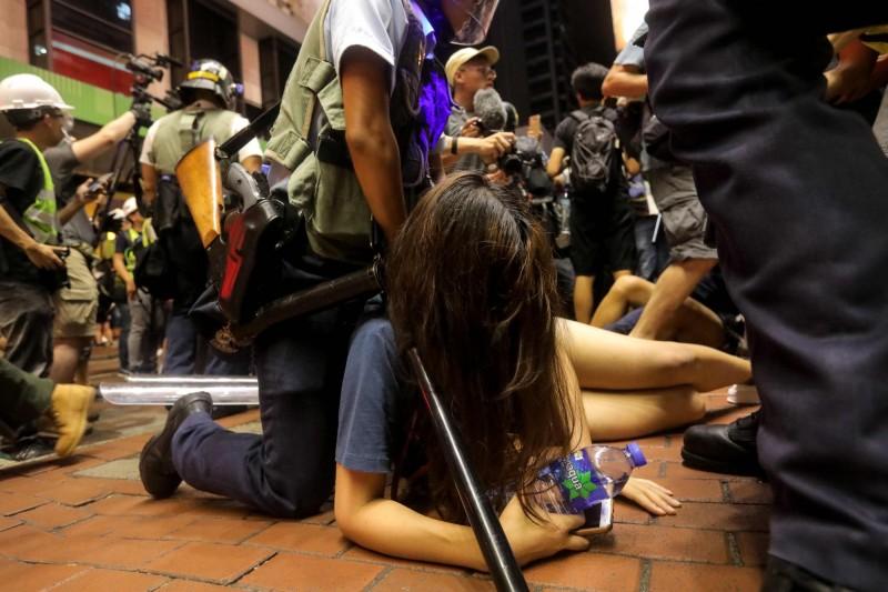 圖為7月7日九龍區遊行,1名遭港警壓制的女示威者。(法新社)