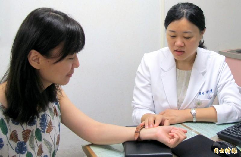 衛福部南投醫院醫師賴卉蓮(右)為患者細心把脈問診情形。(記者謝介裕攝)