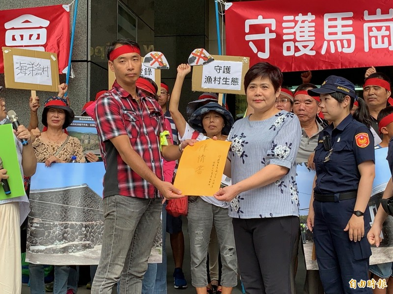 「馬岡街27號咖啡小館」經營人、本案提報人游伯軒(左)向文化局主秘翁玉琴送上陳情書。(記者陳心瑜攝)