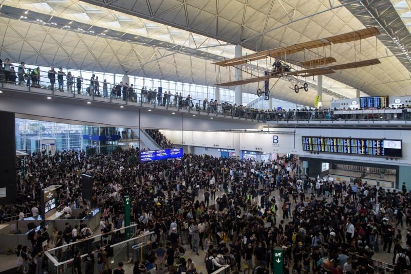 香港「反送中」昨(11)日爆發激烈警民衝突,一名女子右眼中彈,香港網友今(12)日發起「警察還眼」行動,塞爆了香港國際機場。(歐新社)