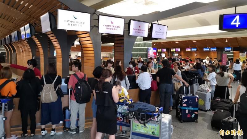 香港機場緊急關閉,台港航班陸續取消,桃園機場出境櫃台擠滿旅客,目前部分業者明晨航班也宣布取消,仍不知何時恢復。(記者姚介修攝)