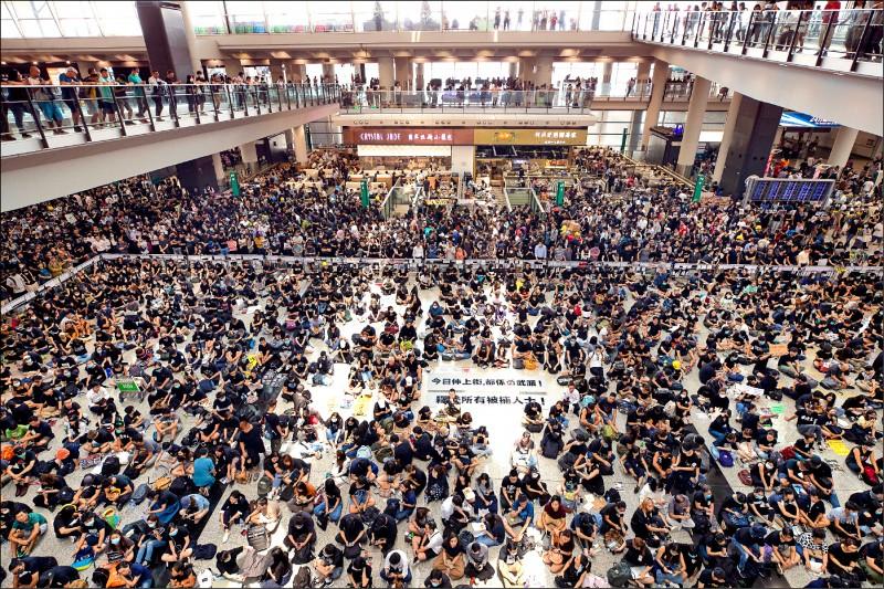 逾萬名憤怒的民眾12日塞爆赤鱲角國際機場,靜坐怒吼「警察暴力、天理不容」,要求「黑警還眼」。(美聯社)