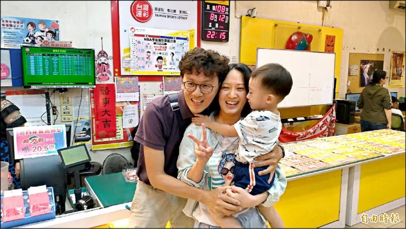 店裡開出威力彩20.47億元頭獎,老闆龐仲凱開心地與妻小抱在一起。(記者王俊忠攝)