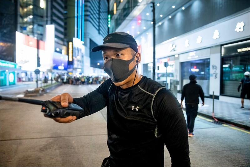香港十一日反送中抗爭期間,疑似警察的男子戴口罩、穿黑衣,喬裝成抗議人士。(彭博)