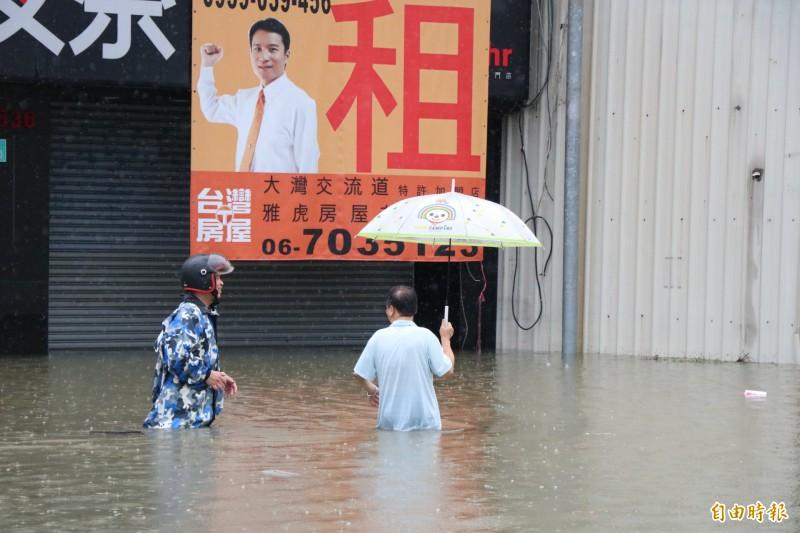 仁德交流道附近淹水嚴重,住戶涉水外出。(記者萬于甄攝)