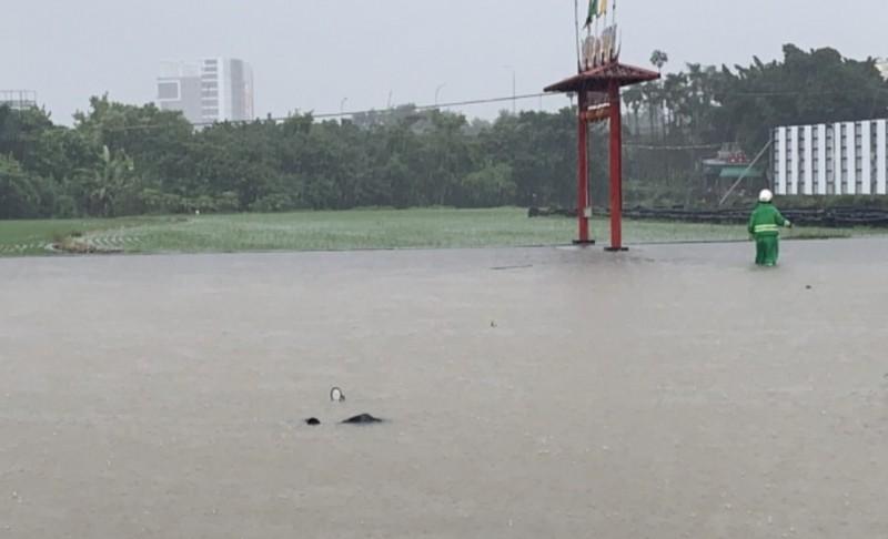 郵差陳志明(畫面右側)送信落水,機車滅頂,他努力涉水把信搬到高處。(讀者提供)