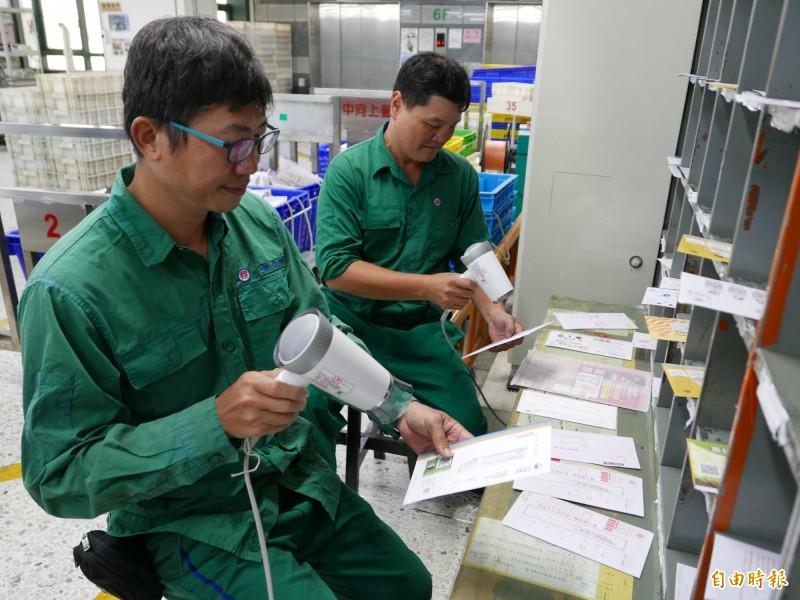 郵差陳志明(左)與同事搶救泡水的信件,就像這樣土法煉鋼把約200封泡水信件一一平放、用吹風機吹乾。(記者蔡淑媛攝)