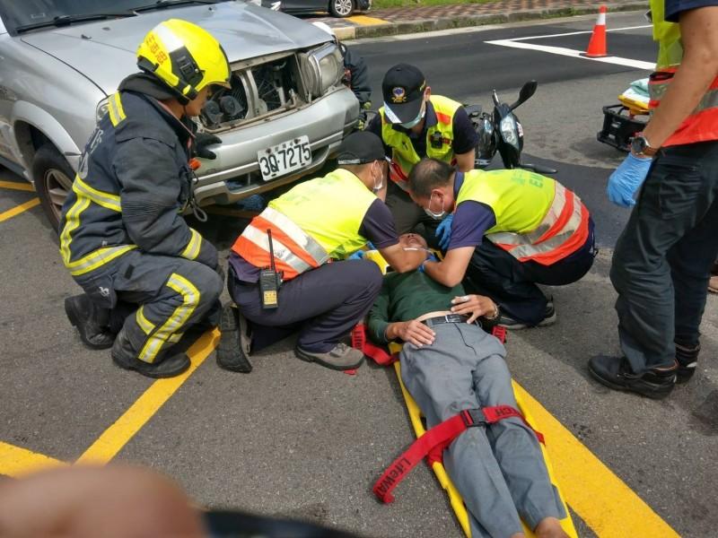 消防人員將柯男從車底救出。(記者歐素美翻攝)