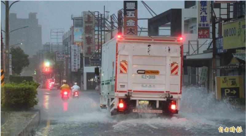 今晨大雨,許多車輛經過濺起水花。(記者萬于甄攝)