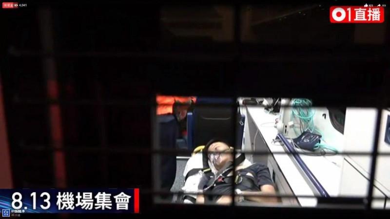 該名疑為中國公安男子被送上救護車後睜開眼睛。(圖擷取自香港《01》直播畫面)