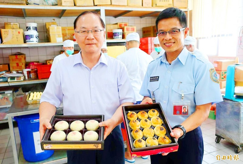 "Changhua Prison Warden Huang Kun-chien, left, and another official on Sunday hold gift boxes of ""iron-bar mooncakes"" and pastries for the Mid-Autumn Festival made by inmates working in the Changhua County prison's bakery. Photo: Chen Kuan-pei, Taipei Times"