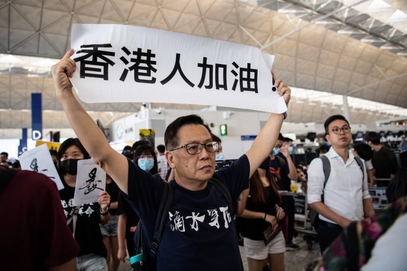 有人手持「香港人加油」標語,聲援在國際機場集會的港人。(歐新社)