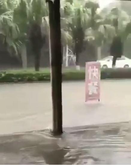 一塊寫著「快餐」的招牌隨著淹水的水流快速前進。(圖擷自爆廢公社)