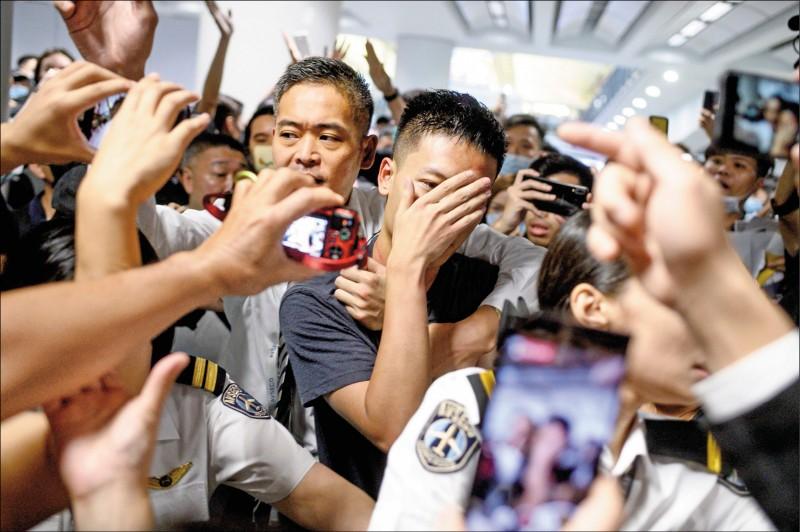 香港機場管理局人員十三日試圖帶走被懷疑是中國公安(圖中)的男子,但遭到示威者攔阻。(法新社)