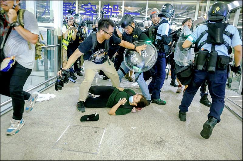 港警在護送疑似中國公安男子就醫途中,動用胡椒噴霧並揮舞警棍,驅離包圍的示威人士。(路透)
