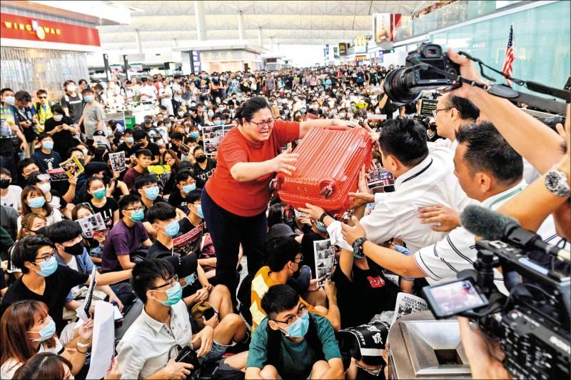 一名在機場大廳雙手高舉行李箱的旅客,13日在地勤人員協助下辦理離境手續。(法新社)
