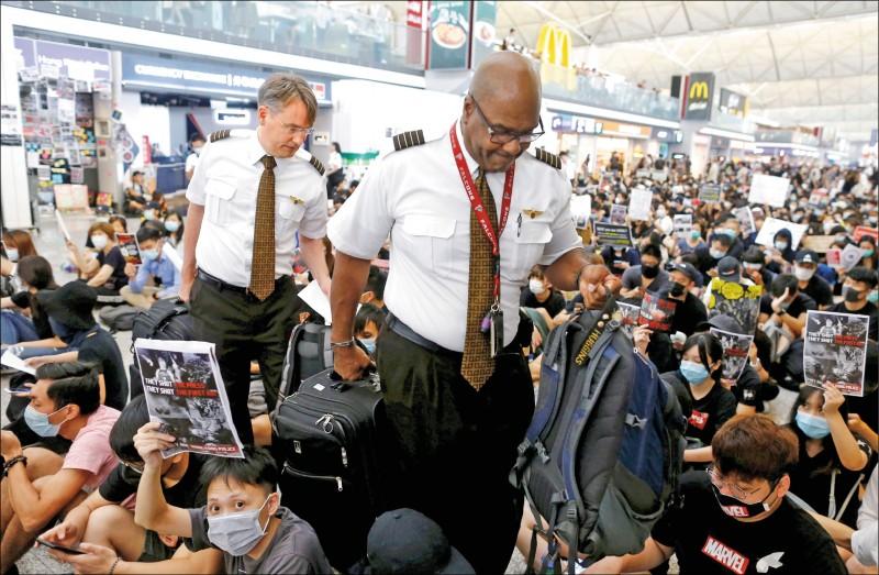 香港赤鱲角國際機場13日湧現逾萬名反送中示威者,機組人員13日通過塞滿機場大廳的黑衣靜坐人群。(路透)