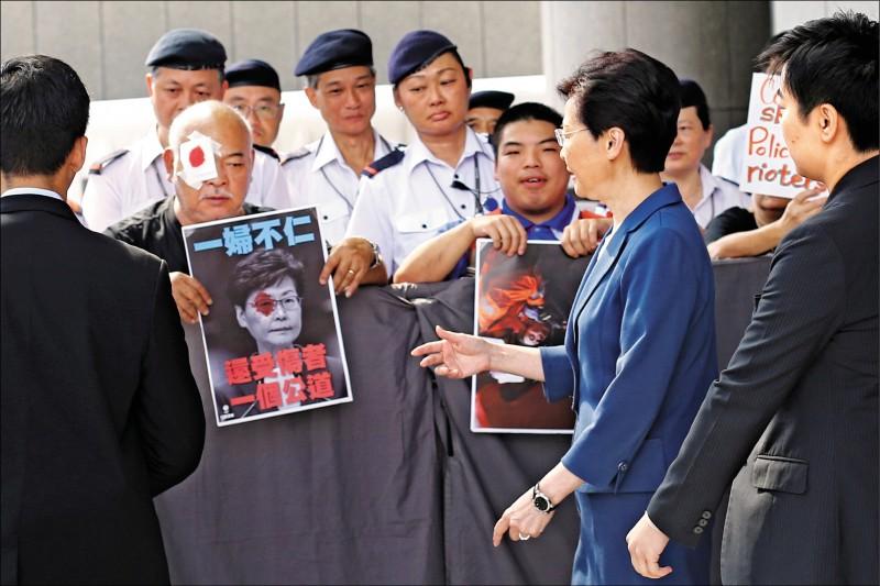抗議人士以紗布遮眼,在林鄭面前諷刺港警使用暴力導致一名女子眼睛受傷。(路透)