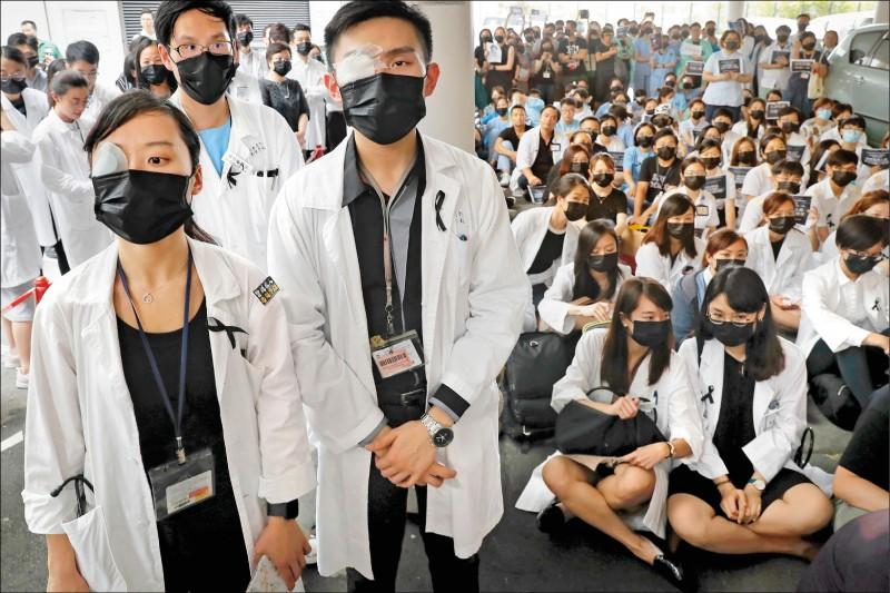 逾千名醫護人員13日配戴黑絲帶、黑色口罩,以紗布蒙眼,在香港13處醫療院所靜坐抗議。(美聯社)