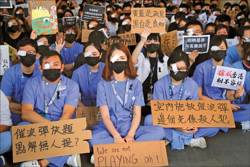 香港逾千名醫護人員13日手持各式標語,靜坐抗議港警執法過當。 (美聯社)