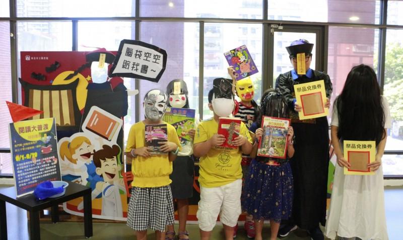 新北市立圖書館江子翠分館推出「閱讀大普度」,準備鬼面具和冥紙造型的祭品兌換券,讓民眾拍照打卡。(新北市立圖書館提供)