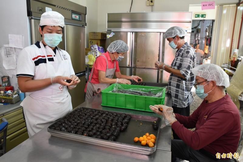 雲林聲暉協進會愛心烘焙坊趕製蛋黃酥,許多志工主動來幫忙。(記者黃淑莉攝)