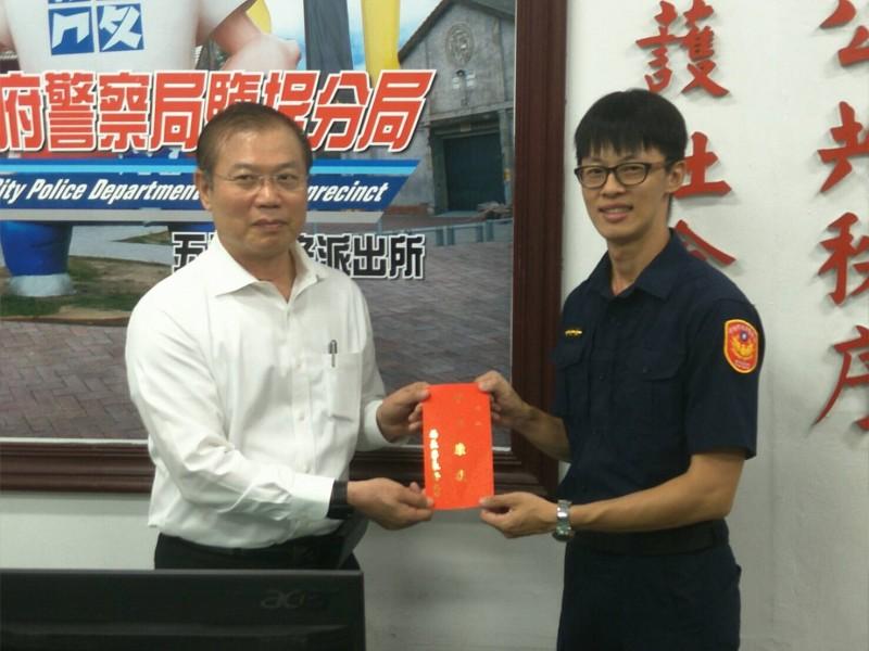 員警顏長弘(右)一起接受局長李永癸(左)表揚。(記者黃良傑翻攝)