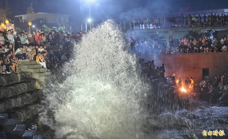 民眾不畏大浪在岸邊觀看鷄籠中元祭放水燈儀式。(記者劉信德攝)