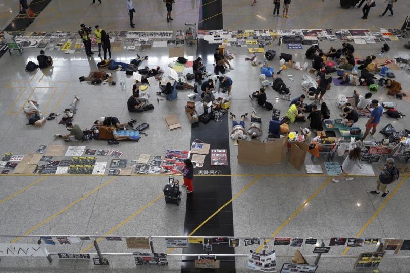 有許多示威者在大廳指定示威區內和平集會,他們坐或躺在大廳地板,擺放宣傳文宣靜坐抗議,引起不少旅客側目。(美聯社)