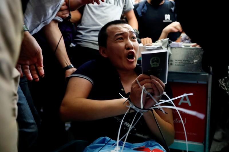 中國環球時報記者付國豪疑混入抗議群眾被發現,遭綁在行李車上。(路透)