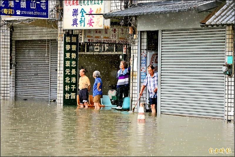 台南仁德昨因強降雨淹成一片,許多住戶在家門張望,期盼積水趕緊消退。(記者萬于甄攝)