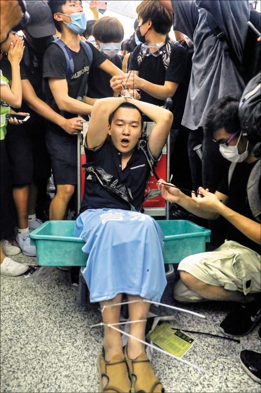 中共黨媒《環球時報》記者付國豪13日深夜在香港赤鱲角國際機場,遭反送中抗爭者以束帶綁在機場行李車上;付國豪身上被搜出中國護照、印有「我愛香港警察」的藍色上衣、記者反光衣等。(美聯社)