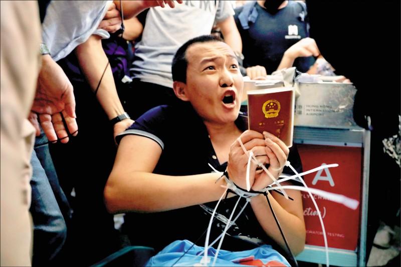 中共黨媒《環球時報》記者付國豪13日深夜在香港赤鱲角國際機場,遭反送中抗爭者以束帶綁在機場行李車上;付國豪身上被搜出中國護照、印有「我愛香港警察」的藍色上衣、記者反光衣等。(路透)