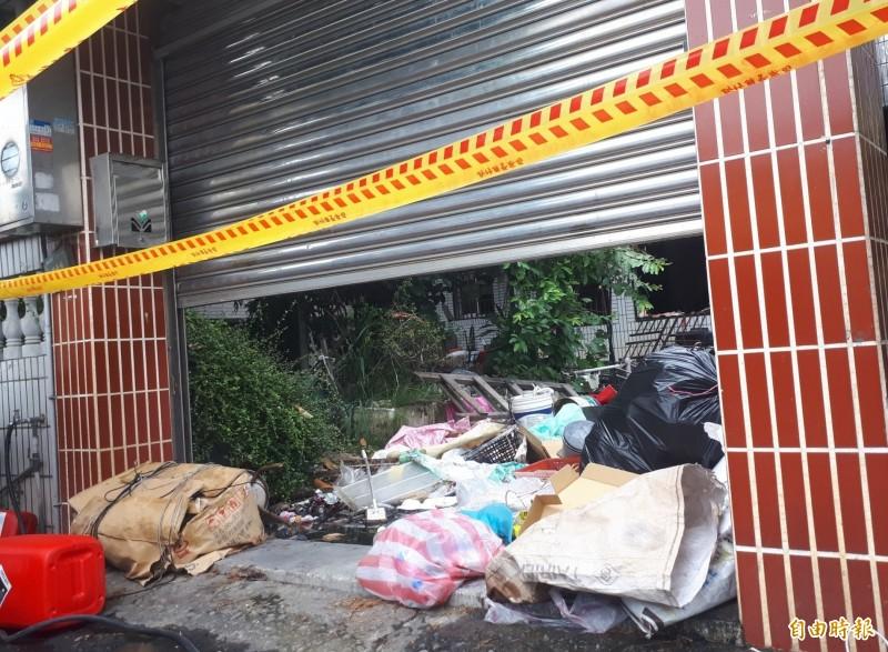 發生火警的透天厝,一樓和庭院堆滿了紙箱、木板、塑膠等各種回收雜物。(記者廖雪茹攝)