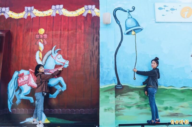 遊客和北門遊客中心彩繪牆互動拍照。(記者楊金城攝)